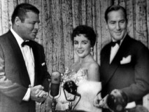 Elizabeth Taylor and her second husband Michael Wilding convey excitement and admiration to brisk interviewer Jack Carson in the Pantages Premiere TV special.