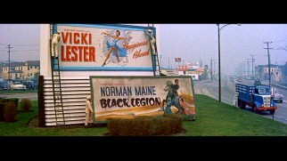 "Out with the old and in with the new: Norman Maine's movie billboard goes down to make way for Vicki Lester's ""Happiness Ahead."" Screencap from the film's original 2000 DVD - click to view in full 720 x 480."
