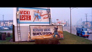 Norman Maine's movie billboard goes down and Vicki Lester's goes up. Screencap from 2010's Deluxe Edition DVD - click to view in full 720 x 480.