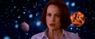 No, astrophysicist Dr. Alex Friedman (Carla Gugino) hasn't chosen the outer space backdrop for her early '90s school photo. She's just being shown the truth about aliens, a task more visually potent with some stars and planets engulfing her.