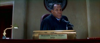 An uncredited Danny Glover plays Honorable Tyrone Kipler, the trial's fair judge.