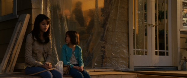 Quimby sisters Beezus (Selena Gomez) and Ramona (Joey King) spend a quiet moment together outside contemplating their parents' hushed tones inside their under-construction home.