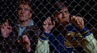 Brothers Jed (Patrick Swayze) and Matt Eckert (Charlie Sheen) are sad to find their hometown under siege and their father on the other side of this fence in Calumet's Drive-In Theater-turned-reeducation camp