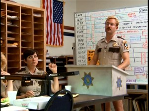 With legs protruding out of his short shorts, Lt. Jim Dangle (Thomas Lennon) conducts the Reno Sheriff's Department daily Morning Briefing.