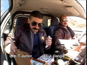 Sunglasses, mustaches, and Coconut Nut Clusters. With dashboard cameras, we often venture into on-duty patrol cars like this one transporting Deputy Travis Junior (Robert Ben Garant) and Lt. Dangle.