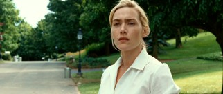 April (Kate Winslet) wears a contemplative expression as she looks down her suburban street.
