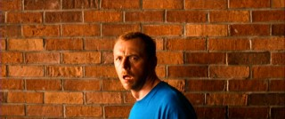 In front of a brick wall, Dennis makes a bewildered open mouth face.