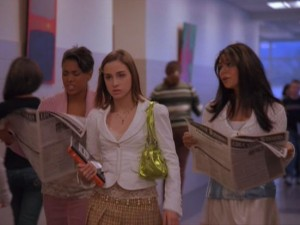 Sawyer (Allison Scagliotti) appears annoyed that the two Jennifers (Falisha Fejoko, Malinda Money) are paying attention to the newspaper and not to her.