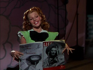 "Rosalind ""Ros"" Bruce (Rita Hayworth) poses with Life magazine in ""Tonight and Every Night."""