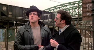 In the role that made him a star, screenwriter Sylvester Stallone portrays Rocky Balboa, a debt enforcer for loan shark Tony Gazzo (Joe Spinell).