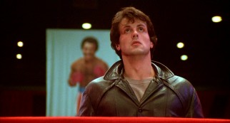 With Apollo Creed smiling behind him, Rocky (Sylvester Stallone) looks up to the rafter at the banner bearing his own likeness.
