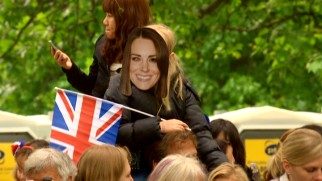 One young sidewalk spectator displays her support with a Flag of the United Kingdom and a cardboard Kate Middleton mask.