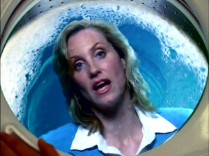 Judith Hoag (the original film April O'Neil) continues to play Marnie's hot mom who is now often seen as an apparition in liquid, such as the laundry washing machine here.