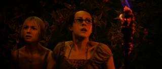 Leading ladies Stacy (Laura Ramsey) and Amy (Jena Malone) wield torch in a dark, red-tinted cave in a scene Benjamin Gates can appreciate.