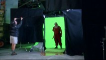 "Santa stands in front of a green screen for a fireplace effects shot, as seen in ""Creating Movie Magic."""