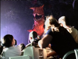 A big red dinosaur frightens park visitors on the thrilling Countdown to Extinction attraction.