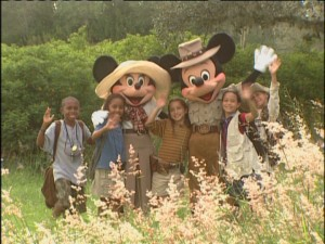 "Decked out in their safari threads, Mickey, Minnie, and the cast of kids wave ""jambo."""