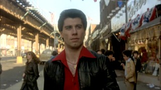 "In the iconic, oft-parodied opening of ""Saturday Night Fever"", Tony Manero (John Travolta) struts along on the sidewalk to the Bee Gees' ""Stayin' Alive"", carrying a paint can and eating two stacked slices of pizza."