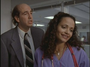 "Sam Lloyd plays Ted, the hospital's eternally sweaty and stressed out lawyer. Judy Reyes plays Nurse Carla Espinosa. Here, they collaborate to sing some Poison for a comatose patient in ""My Heavy Meddle."""