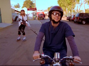 J.D. (Zach Braff) pulls roommate/pal Elliot (Sarah Chalke) while driving his scooter Sasha.