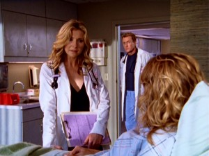 Private physician Elliot (Sarah Chalke) talks with a patient while Dr. Cox (John C. McGinley) sneaks in to observe.