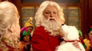 "The bad news: Santa Claus (Richard Riehle) has just found out his old friend has died. The awesome news: he's just gotten this stuffed ""toy"" dog out of it."