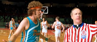 "Flint Tropics player/coach/owner Jackie Moon (Will Ferrell) disputes a call made by referee/priest Father Pat (Matt Walsh) in the ABA comedy ""Semi-Pro."""