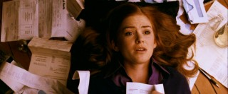 Becky (Isla Fisher) lays down in a sea of a receipts and credit card statements, as all credit card debt victims do.
