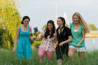 Being young ladies, this foursome naturally walks through high grass while giggling.