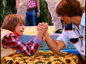 Cody uses a drawing compass protractor to calculate the optimal angle for beating Bailey's boyfriend Moose (Hutch Dano) in a Mulch Festival arm wrestling match.