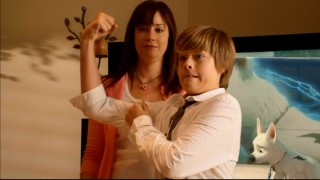 "One of the Sprouse boys shows off the high definition of his right bicep while Kim Rhodes and Disney's Bolt look on in the ""Blu-ray is Suite!"" short infomercial."