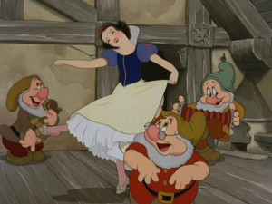 Snow White dances merrily with the Dwarfs in a room conveniently tall enough for her to move around in.