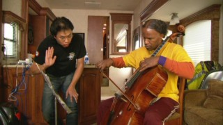 "Music technical consultant Ben Hong gives actor Jamie Foxx some cello pointers in ""An Unlikely Friendship."""