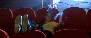 "Pre-teen troublemaker Lee Carter (Will Poulter) smokes in the No Smoking theatre section he has to himself while bootlegging ""First Blood."""
