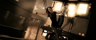 Gold tinting establishes this scene of Denny Colt (Johnny Simmons) and Sand Saref (Seychelle Gabriel) playing on an elevated subway train as a flashback. So do the younger actors and less complicated relationship.
