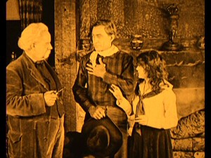 "Ranch hand Cheyenne Harry (Harry Carey, center) and his girlfriend Helen (Molly Malone) bring news of their engagement to his boss a.k.a. her father, the Twainian L.M. Wells in the 1917 John Ford silent film ""Bucking Broadway."""