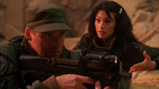 Lt. Col. Cameron Mitchell (Ben Browder) brandishes an automatic assault riffle in the midst of a serious debate with Vala (Claudia Black).