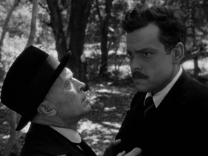 The mind of Professor Charles Rankin (Orson Welles, right) appears to be wandering as Konrad (Konstantin Shayne) warns him of trouble.