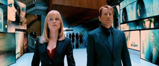"Agents Peters (Radha Mitchell) and Greer (Bruce Willis) take a purposeful stroll through surrogate manufacturer Virtual Self Industries' sleek lobby in Jonathan Mostow's ""Surrogates."""