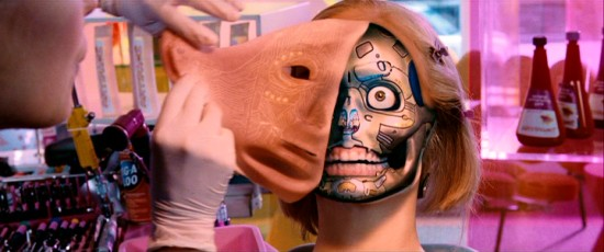 At a beautician's cosmetic shop, a surrogate's face peels right off to reveal the robotic skeleton below.