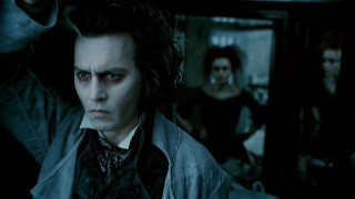 Brooding Sweeney Todd (Johnny Depp) looks out the window of the barbershop he's reclaimed from Mrs. Lovett (Helena Bonham Carter, rear).