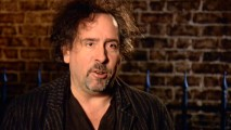 "Director Tim Burton speaks in front of fence and brick in ""The Making of 'Sweeney Todd...'."""