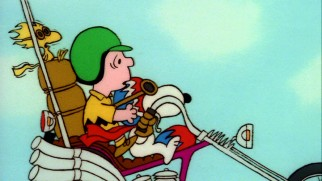 Charlie Brown gets a motorcycle ride to Camp Remote courtesy of Snoopy and Woodstock.