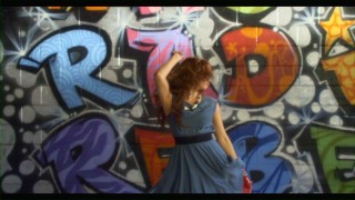 "Debby Ryan dances in front of promotional graffiti in her ""We Got the Beat"" music video."