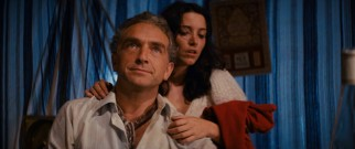 Marion (Karen Allen) clings to Belloq (Paul Freeman), a nemesis keeping her safe.