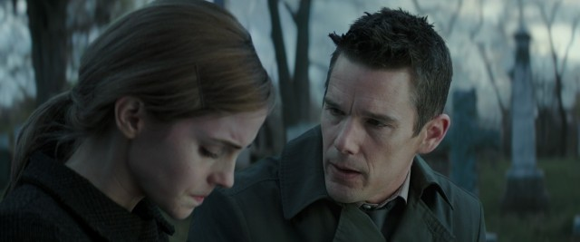 Detective Bruce Kenner (Ethan Hawke) consoles Angela Gray (Emma Watson) by the grave of her mother.