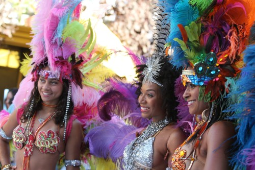 Three flamboyantly-costumed samba dancers smile for the cameras.
