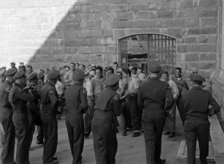 "State police officers wielding guns move in on rioting prisoners brandishing homemade weapons in ""Riot in Cell Block 11."""