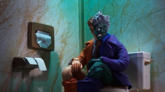 Even on the toilet, Two-Face flips his trusty coin to make decisions for him.