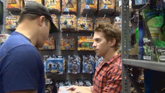 "Geoff Johns and Seth Green raid and admire the wealth of toys they encounter on their ""DC Entertainment Tour."""